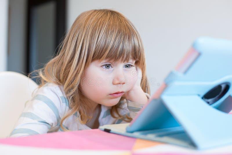 Étonnez l'expression du petit enfant observant le comprimé numérique photos libres de droits