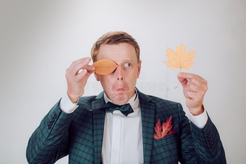 Étonnez l'homme de tête de lecture jouant avec des feuilles et regardant l'appareil-photo Homme de surprise Gens fous Autumn Time images libres de droits