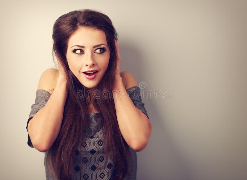 Étonnez la belle femme de maquillage tenant la tête les mains et le looki image stock