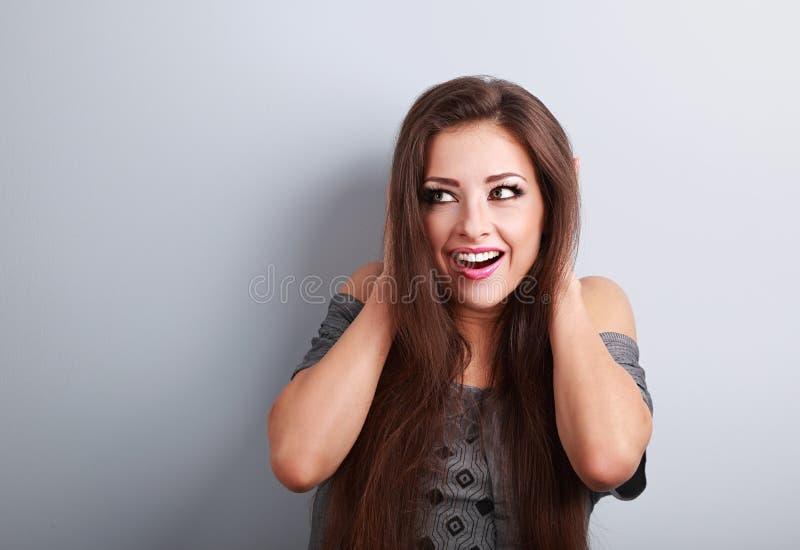 Étonnez la belle femme de maquillage tenant la tête les mains et le looki photographie stock