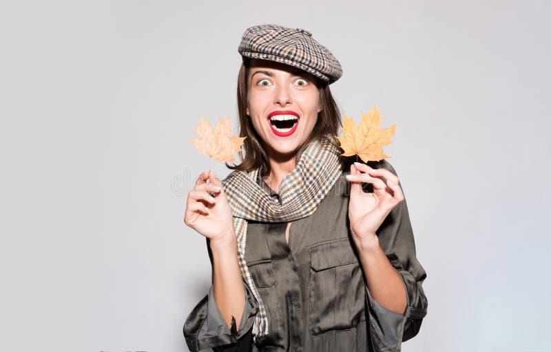 Étonnez la femme jouant avec des feuilles et regardant l'appareil-photo L'automne célèbrent La jeune femme heureuse se préparent  photos libres de droits