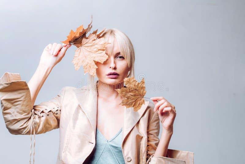 Étonnez la femme jouant avec des feuilles et regardant l'appareil-photo Fille en automne jouant avec des feuilles sur le fond de  image libre de droits