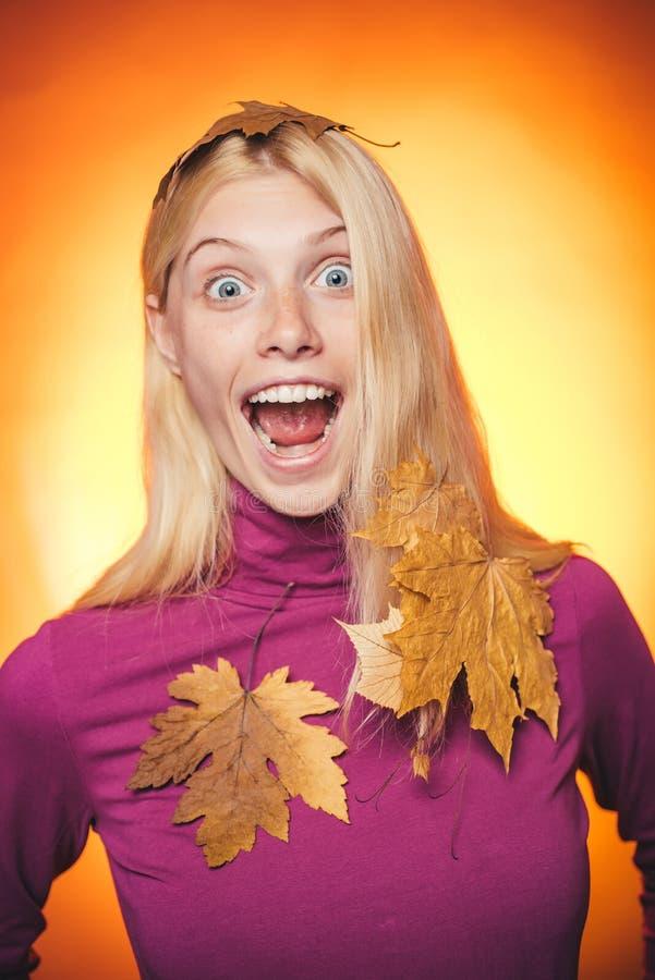 Étonnez la femme jouant avec des feuilles et regardant l'appareil-photo La jeune femme heureuse se préparent au jour ensoleillé d image libre de droits