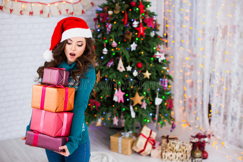 Étonnez la jeune belle femme avec des cadeaux près d'un arbre de Noël An neuf image stock