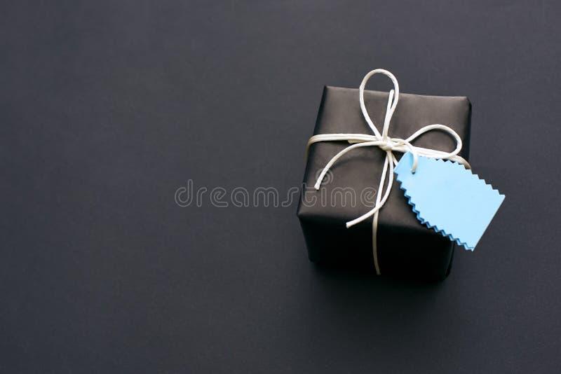 Étonnez-le ! Boîte-cadeau noir élégant avec un peu d'arc sur le fond foncé image stock