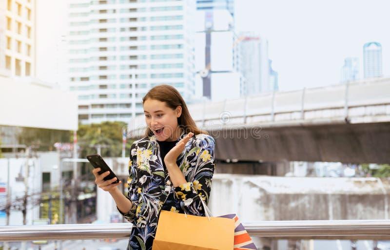 Étonnez les achats de femme en ligne et les paniers de participation dans la rue de ville, concept de mode de vie photos stock