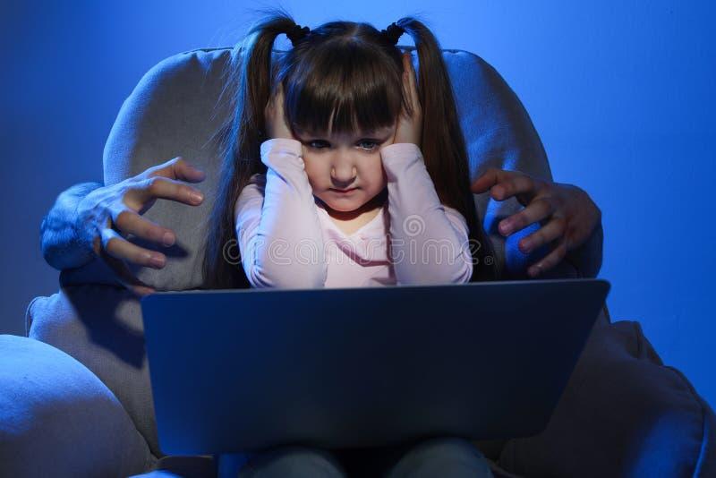 Étranger atteignant le petit enfant effrayé avec l'ordinateur portable Danger de Cyber image stock