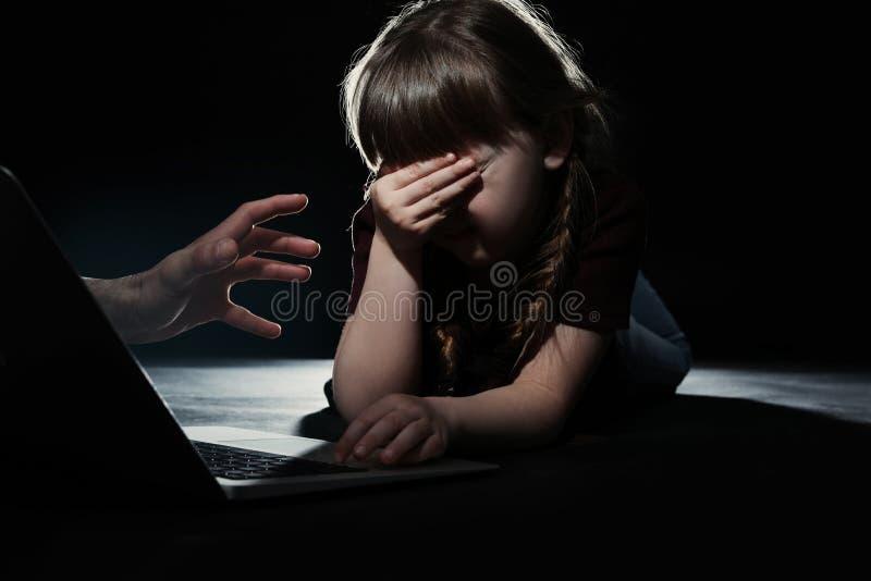Étranger atteignant le petit enfant effrayé avec l'ordinateur portable Danger de Cyber photo stock
