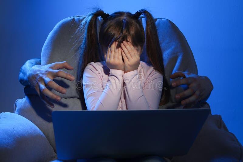 Étranger atteignant le petit enfant effrayé avec l'ordinateur portable sur le fond de couleur photo libre de droits