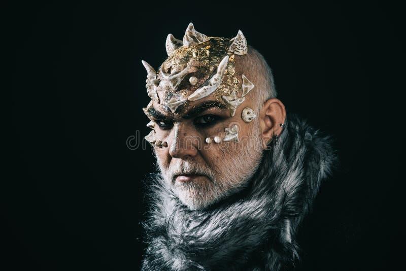 Étranger, démon, maquillage de sorcier L'homme supérieur avec la barbe blanche s'est habillé comme le monstre Démon sur le fond n image libre de droits