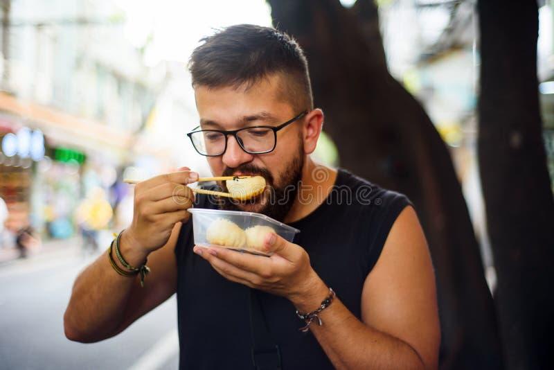 Étranger mangeant de la nourriture de rue en Chine images libres de droits