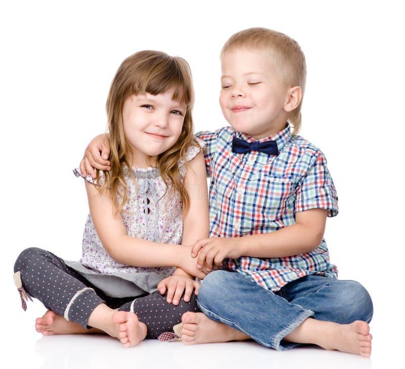 Étreindre de frère de sourire et de petite soeur D'isolement sur le blanc images stock