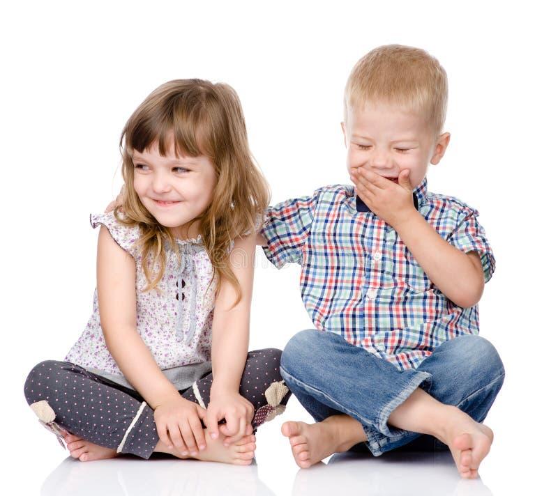 Étreindre de frère de sourire et de petite soeur Sur le blanc images stock