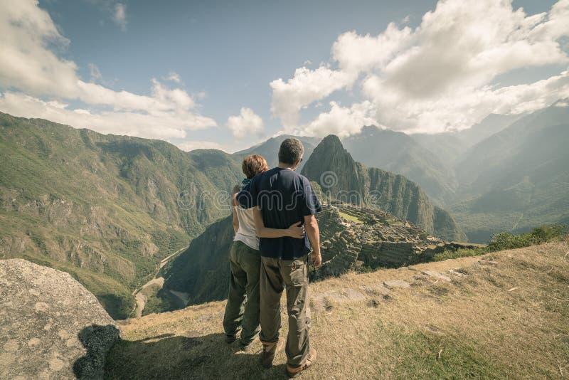 Étreindre des couples regardant Machu Picchu, le Pérou, image modifiée la tonalité photographie stock libre de droits