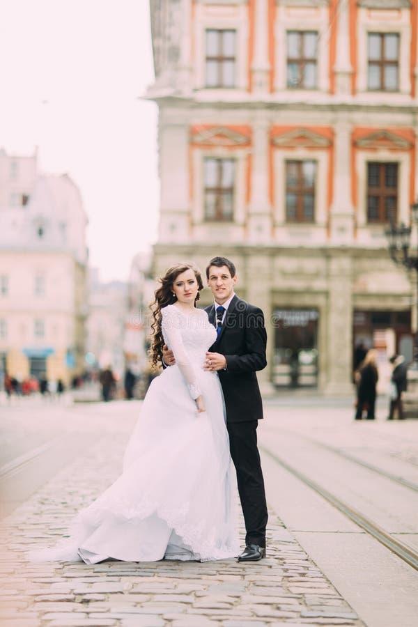 Étreindre fonctionnant de jeune mariée heureuse et de marié élégant sur la vieille ville ensoleillée de fond photo stock