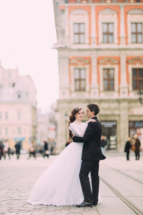 Étreindre fonctionnant de jeune mariée heureuse et de marié élégant sur la vieille ville ensoleillée de fond images stock