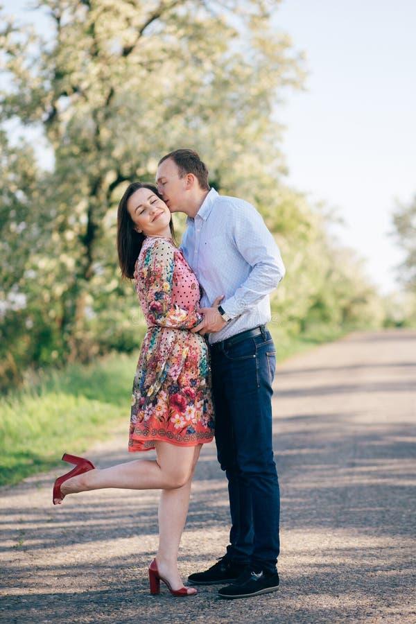 Étreindre sensuel de beaux jeunes couples et embrasser sur la route en soleil parmi le gisement et les arbres de ressort Famille  images stock