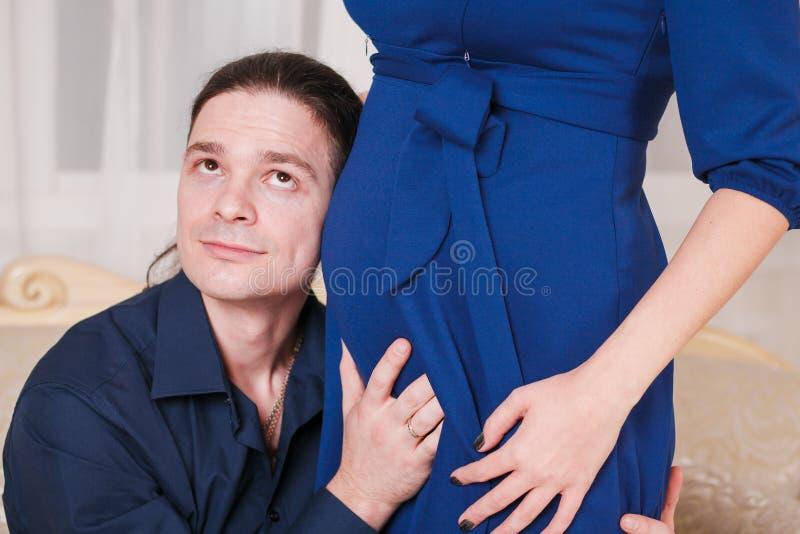 Étreint la main de l'homme enceinte de ventre image stock