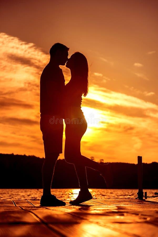 Étreinte d'amour de couples, silhouette au lever de soleil images stock