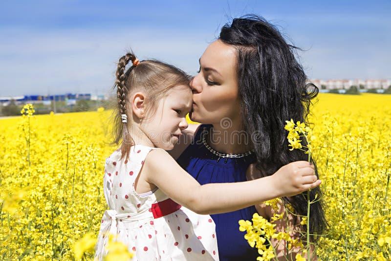 Étreinte heureuse de fille de mère et d'enfant de famille sur les fleurs jaunes image stock