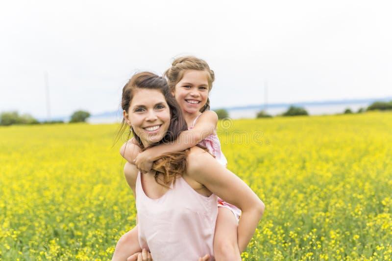 Étreinte heureuse de fille de mère et d'enfant de famille sur les fleurs jaunes sur la nature en été photo stock