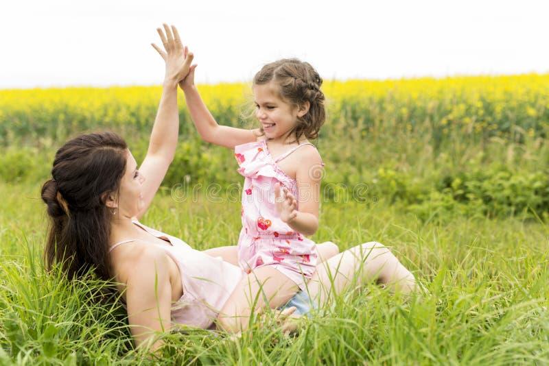 Étreinte heureuse de fille de mère et d'enfant de famille sur les fleurs jaunes sur la nature en été photo libre de droits