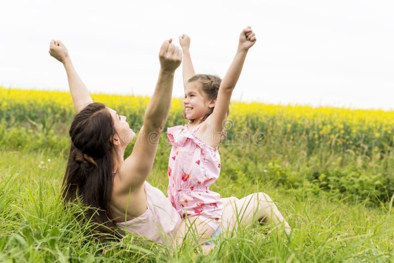 Étreinte heureuse de fille de mère et d'enfant de famille sur les fleurs jaunes sur la nature en été images stock