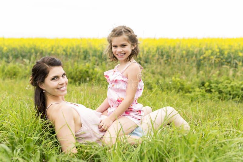 Étreinte heureuse de fille de mère et d'enfant de famille sur les fleurs jaunes sur la nature en été photos libres de droits