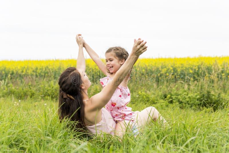 Étreinte heureuse de fille de mère et d'enfant de famille sur les fleurs jaunes sur la nature en été images libres de droits