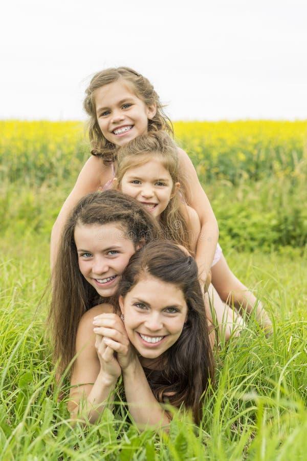 Étreinte heureuse de mère de famille et de fille de childs sur les fleurs jaunes sur la nature en été photo libre de droits