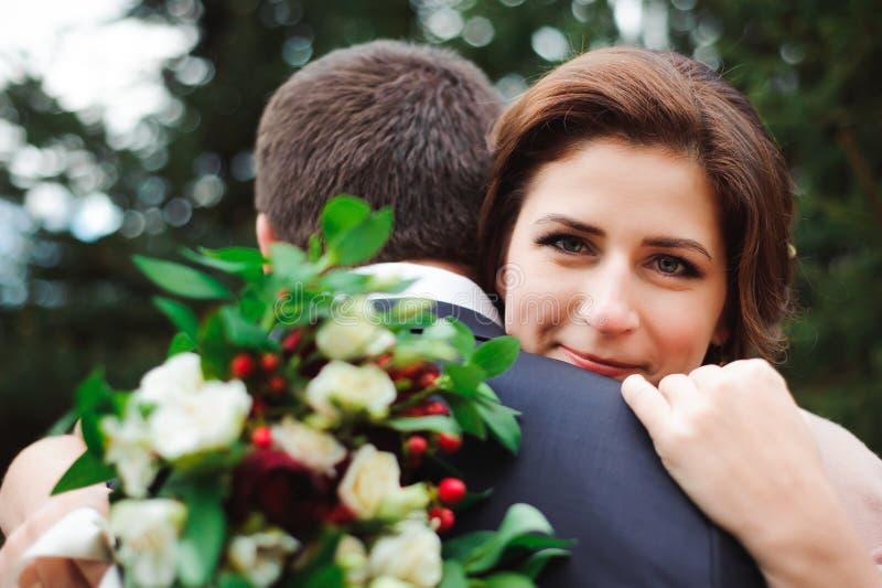 Étreinte romantique des nouveaux mariés Le couple marche en stationnement photo libre de droits