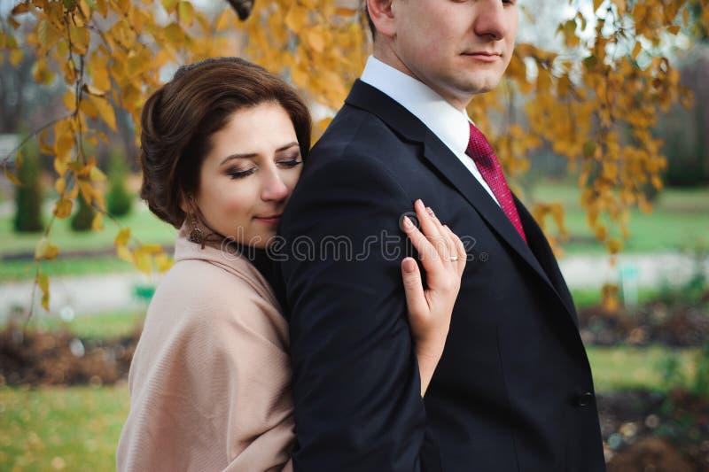Étreinte romantique des nouveaux mariés Le couple marche en stationnement image stock