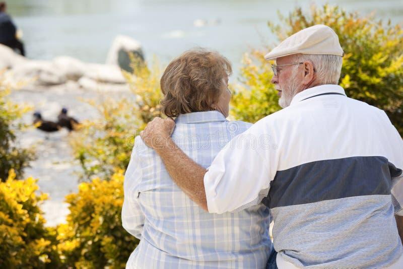 Étreinte supérieure de couples sur un banc en parc image stock