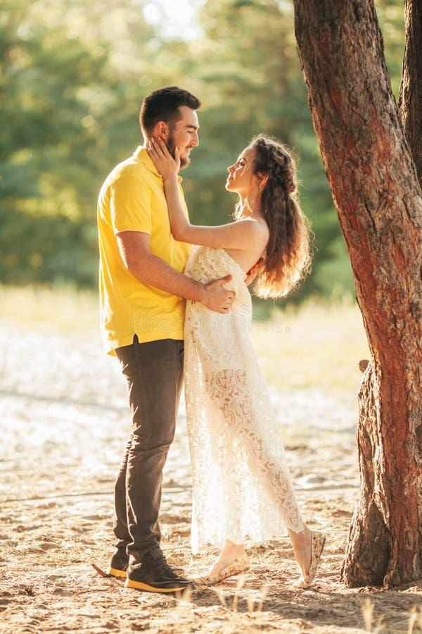 Étreintes de couples enamourées par jeunes dans la forêt images stock