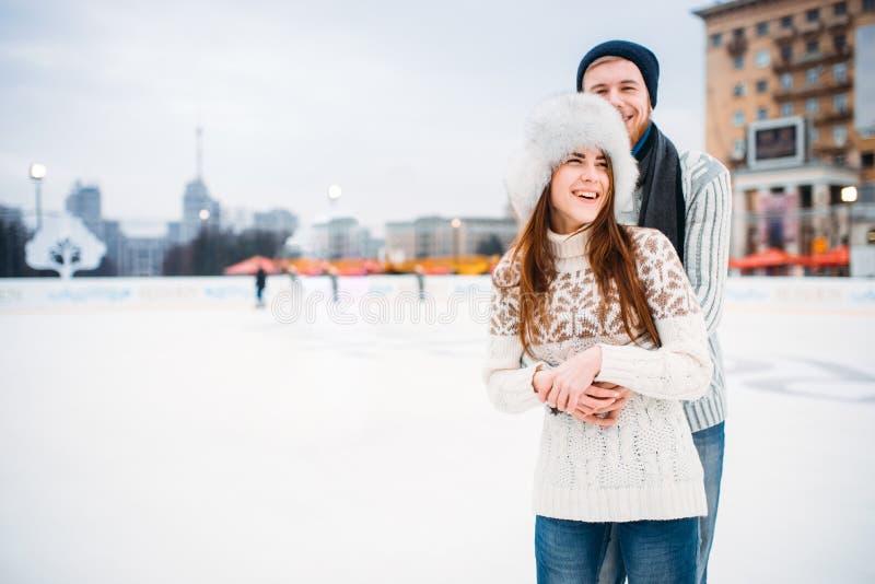 Étreintes heureuses de couples d'amour sur la piste de patinage image libre de droits
