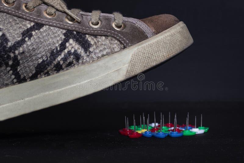 étroit d'une chaussure de femme qui est sur le point de faire un pas sur quelques aiguilles image libre de droits