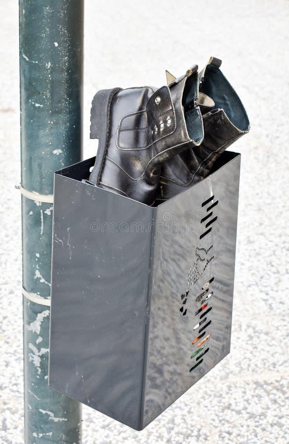 étroit d'une paire de bottes noires utilisées faites en cuir noir abandonné dans une poubelle noire Bottes et poubelle à un courr photos libres de droits