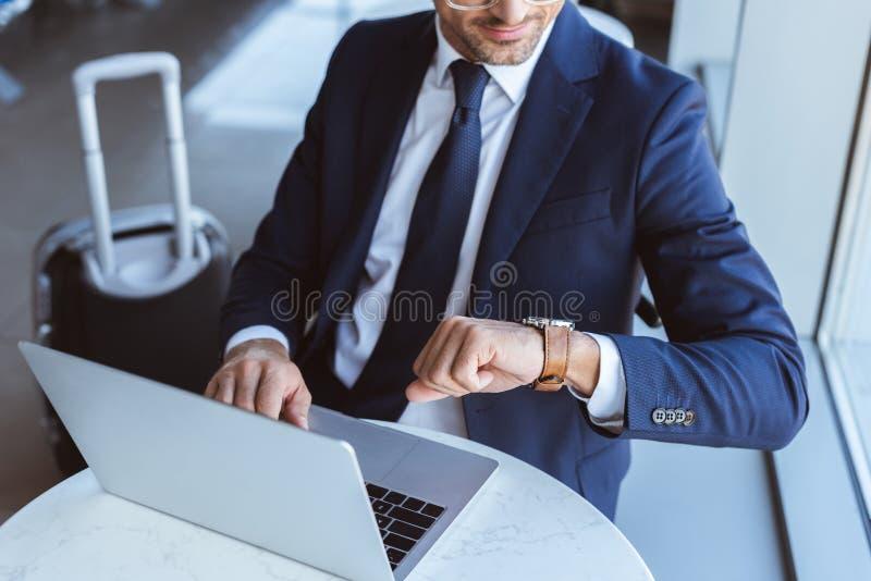 étroit de l'homme d'affaires en verres utilisant l'ordinateur portable et de regarder la montre images stock