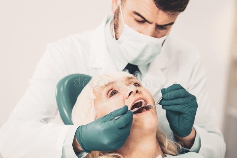 Étroit du docteur vérifiant des dents de dame âgée photos libres de droits