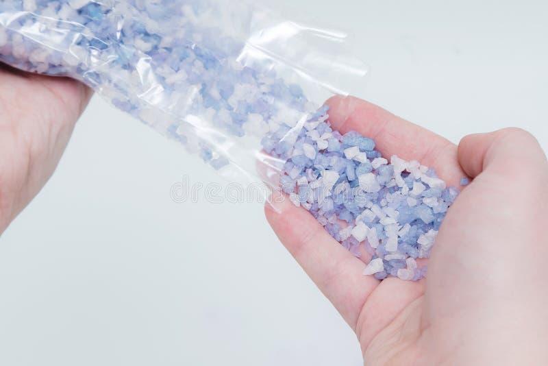 Étroitement des cristaux étudiants à fond de sel de bain de la main de la femme dans l'eau Traitement de station thermale, relaxa images stock