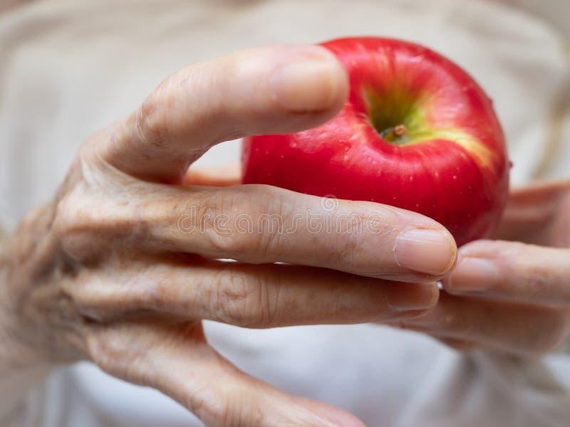 Étroitement des mains de la femme agée tenant Apple rouge photos stock