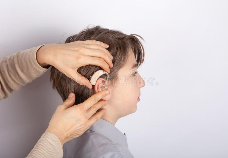 Étroitement des mains du docteur insérant la prothèse auditive dans l'oreille d'un patient de garçon de youg photo libre de droits