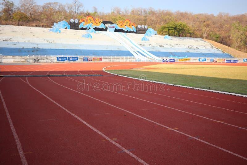Étroitement, le plancher courant rouge de voie a les lignes blanches dans le stade extérieur pour le fond images stock
