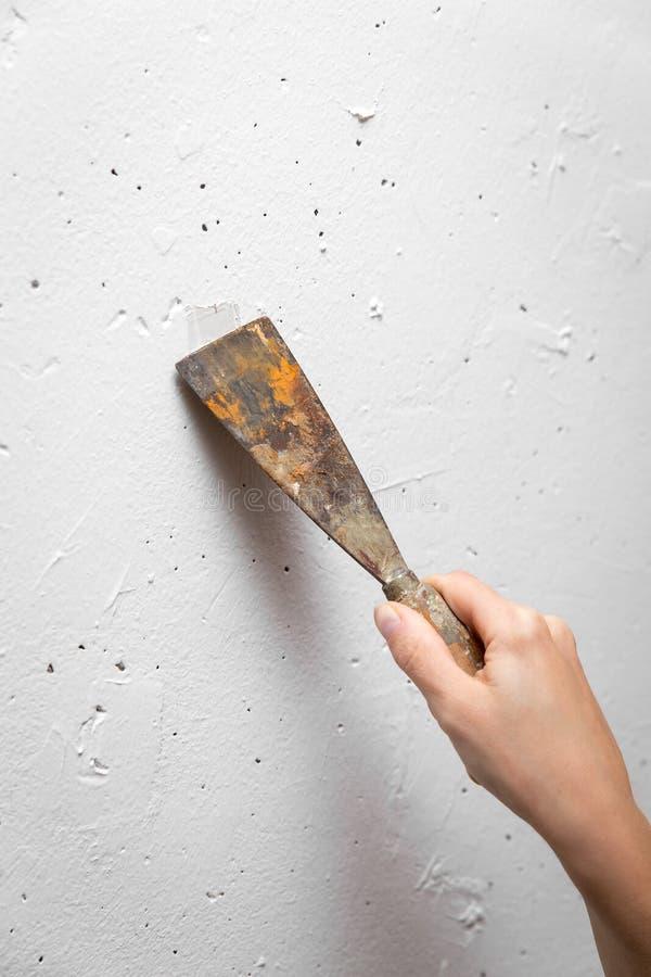 Étroitement, main de femme avec le couteau de mastic réparant un mur, handywoman, rénovation image libre de droits