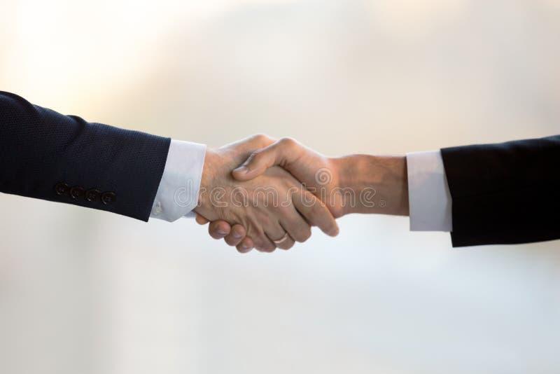 Étroitement vers le haut de deux hommes d'affaires dans les costumes se serrant la main photo stock