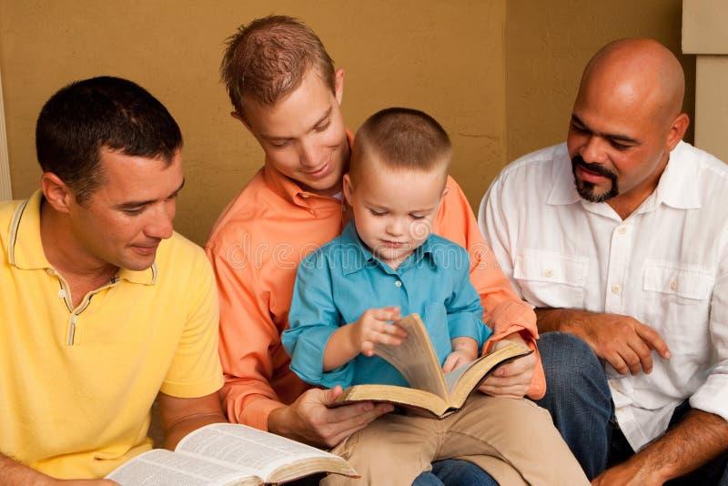 Étude de bible de groupe du ` s d'hommes Père lisant la bible avec son fils image libre de droits