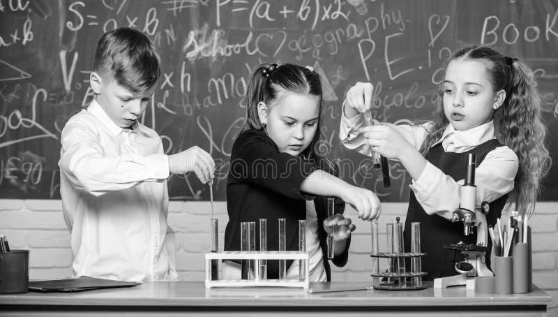 Étude des états liquides Les élèves des écoles de groupe étudient les liquides chimiques Laboratoire scolaire Les filles et les g images stock