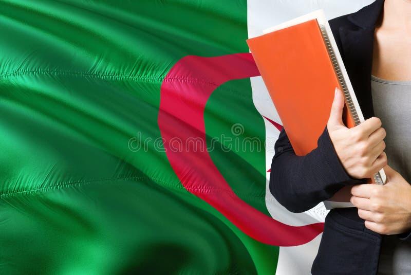 Étude du concept algérien de langue Position de jeune femme avec le drapeau de l'Algérie à l'arrière-plan Professeur tenant des l photographie stock