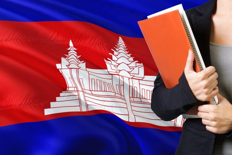 Étude du concept cambodgien de langue Position de jeune femme avec le drapeau du Cambodge à l'arrière-plan Professeur tenant des  photos stock