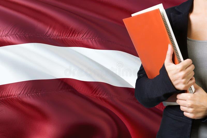 Étude du concept letton de langue Position de jeune femme avec le drapeau de la Lettonie à l'arrière-plan Professeur tenant des l photographie stock